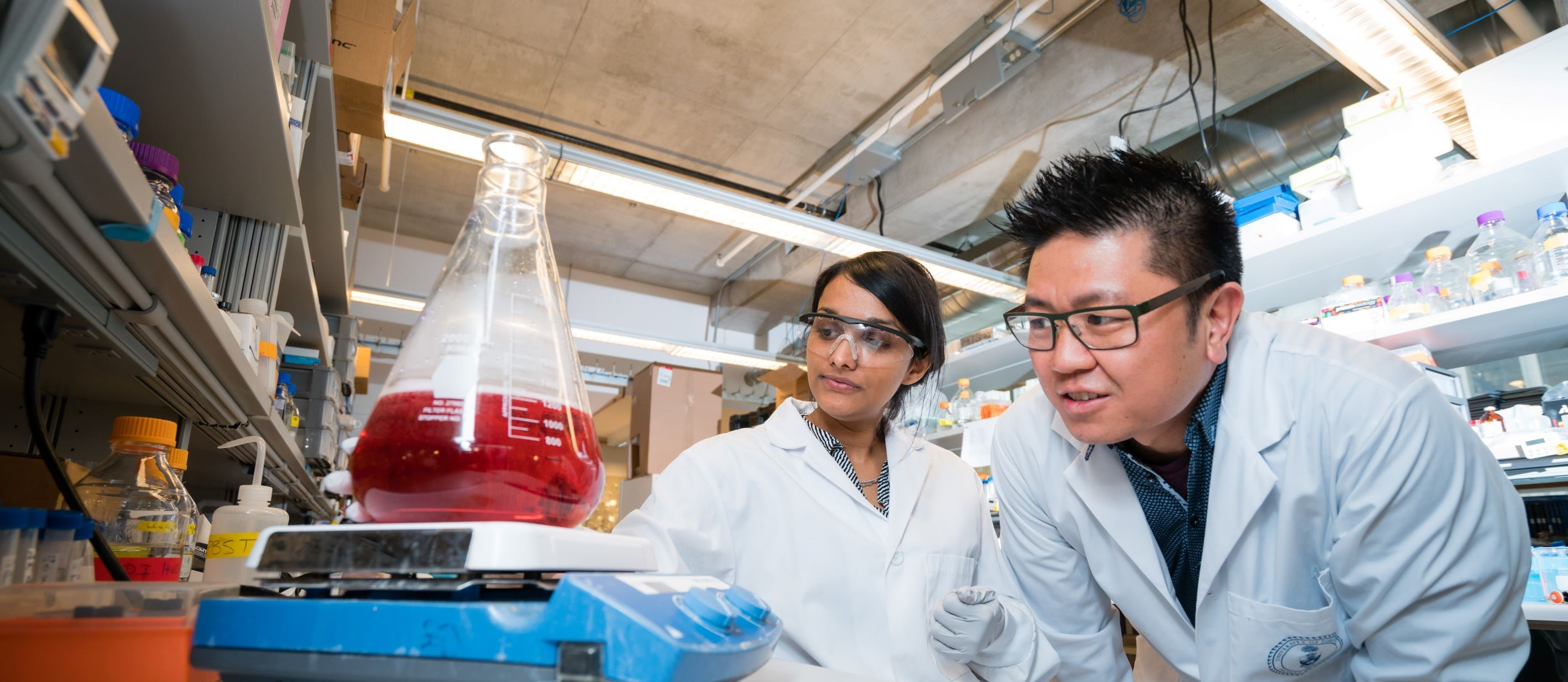 Warren Chan and student examining reagent in lab